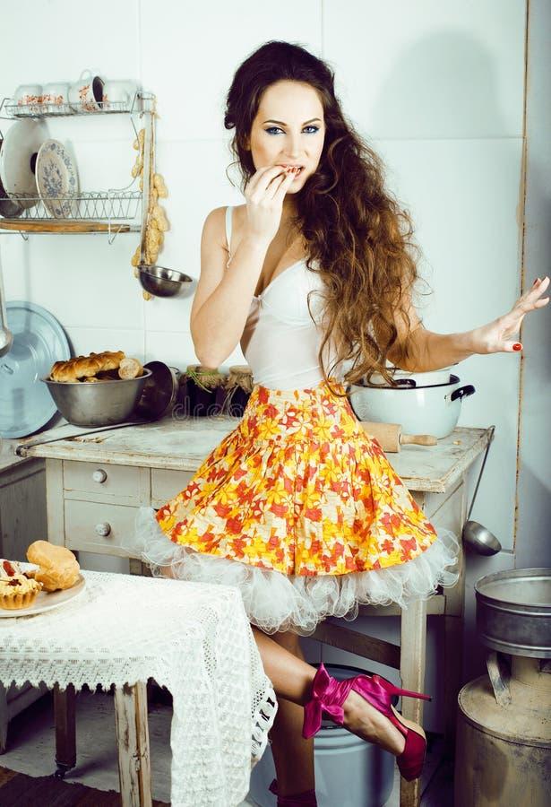 Femme au foyer folle de vraie femme sur la cuisine, mangeant perfoming, bizare images stock