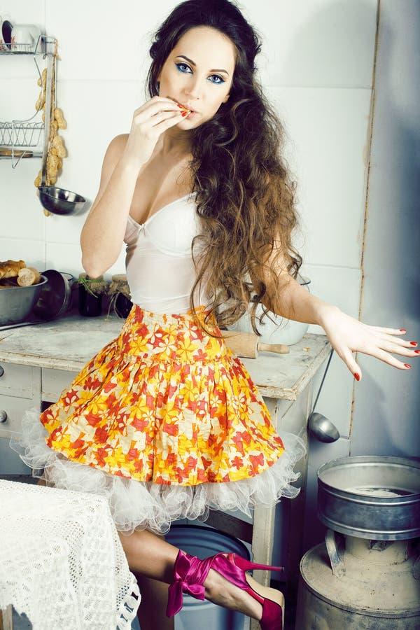 Femme au foyer folle de vraie femme sur la cuisine, mangeant perfoming, fille de bizare image stock