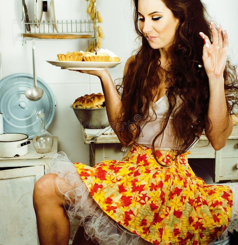 Femme au foyer folle de vraie femme sur la cuisine, mangeant perfoming, fille de bizare photographie stock