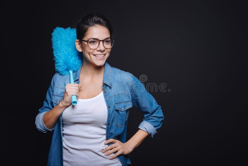 Femme au foyer gaie tenant la brosse de saupoudrage photographie stock