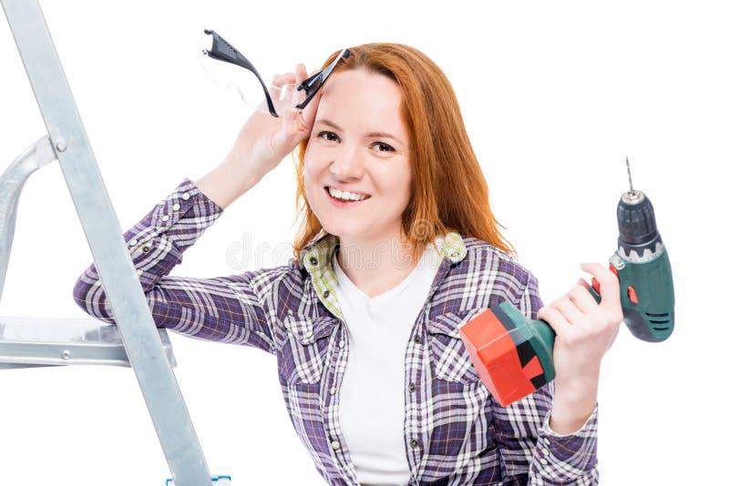 Femme au foyer heureuse avec des outils utilisant une chemise de plaid image stock