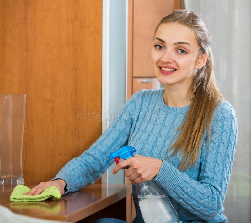 Femme au foyer heureuse dans la table de saupoudrage de chandail dans le salon image libre de droits