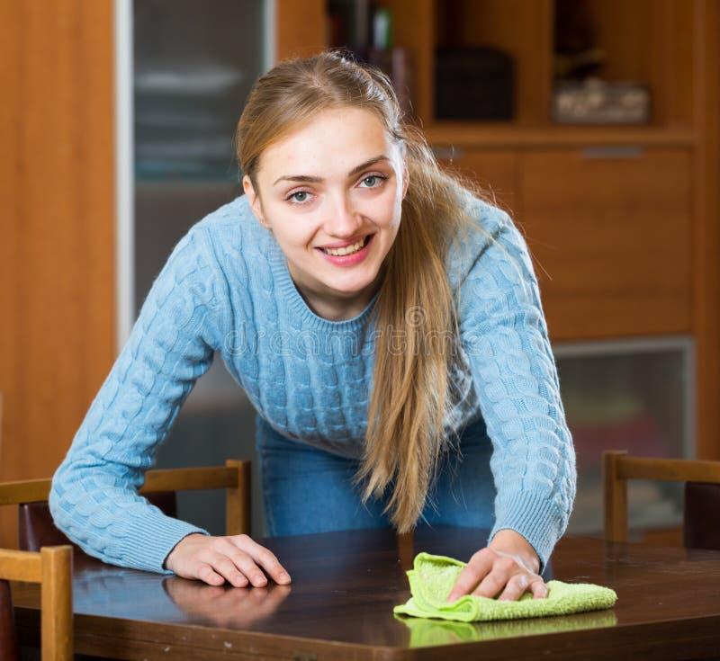 Femme au foyer heureuse dans la table de saupoudrage de chandail dans le salon image stock