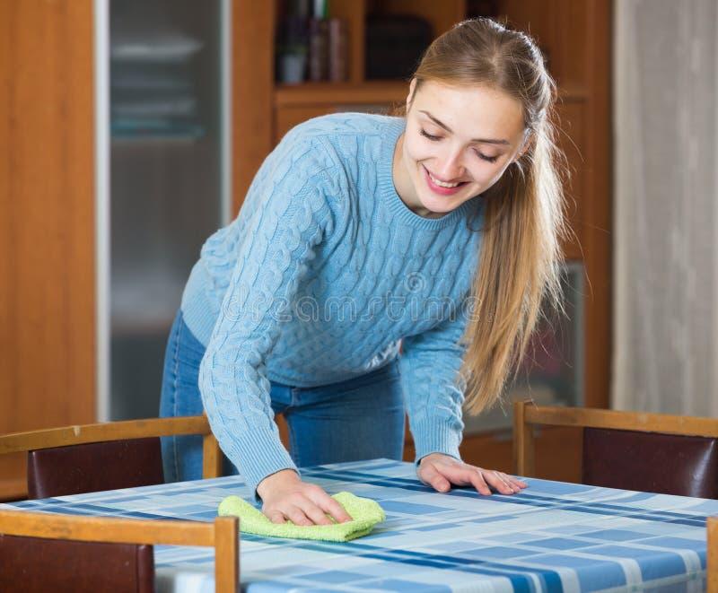 Femme au foyer heureuse dans la table de saupoudrage de chandail dans le salon images libres de droits