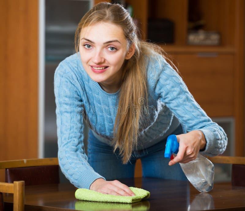 Femme au foyer heureuse dans la table de saupoudrage de chandail dans le salon photographie stock