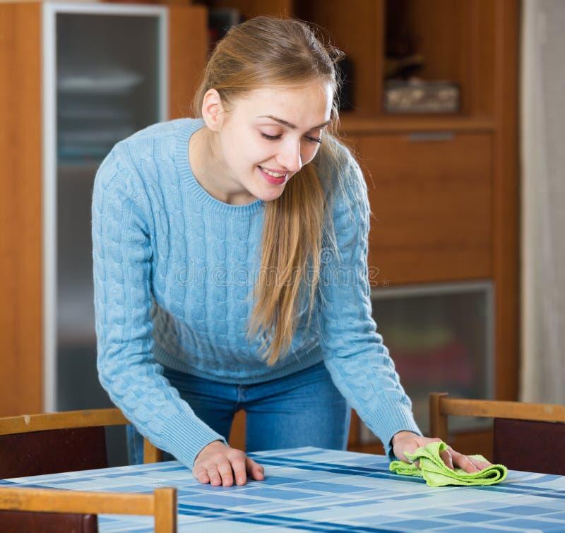 Femme au foyer heureuse dans la table de saupoudrage de chandail dans le salon photo stock