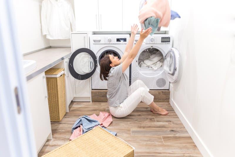 Femme au foyer heureuse de mère de famille dans la buanderie avec les vêtements de lancement de machine à laver  photo stock
