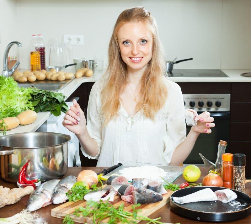 Femme au foyer heureuse faisant cuire des poissons en farine photos libres de droits