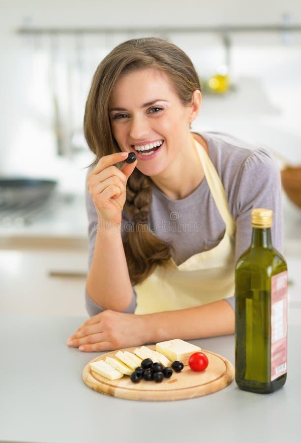 Femme au foyer heureuse mangeant du fromage avec des olives image libre de droits