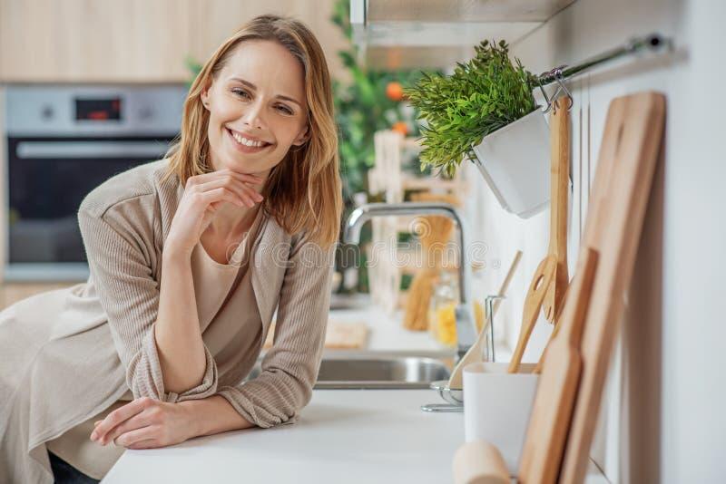 Femme au foyer joyeuse rêvant du dîner parfait photographie stock