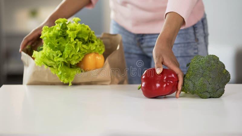 Femme au foyer mettant des légumes sur la table du sac d'épicerie, nutrition saine photographie stock