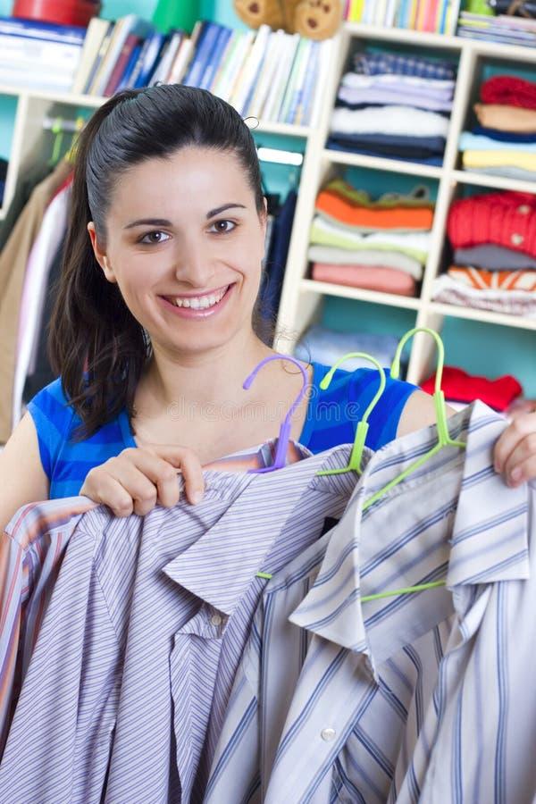 Femme au foyer mettant des vêtements sur l'espace disponible photo libre de droits