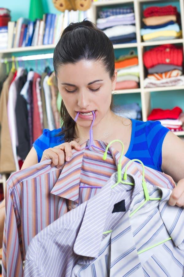 Femme au foyer mettant des vêtements sur l'espace disponible photos stock
