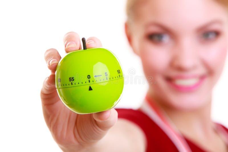Femme au foyer ou chef heureuse dans le tablier de cuisine montrant la minuterie de pomme photos libres de droits