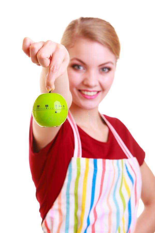 Femme au foyer ou chef heureuse dans le tablier de cuisine montrant la minuterie de pomme images libres de droits
