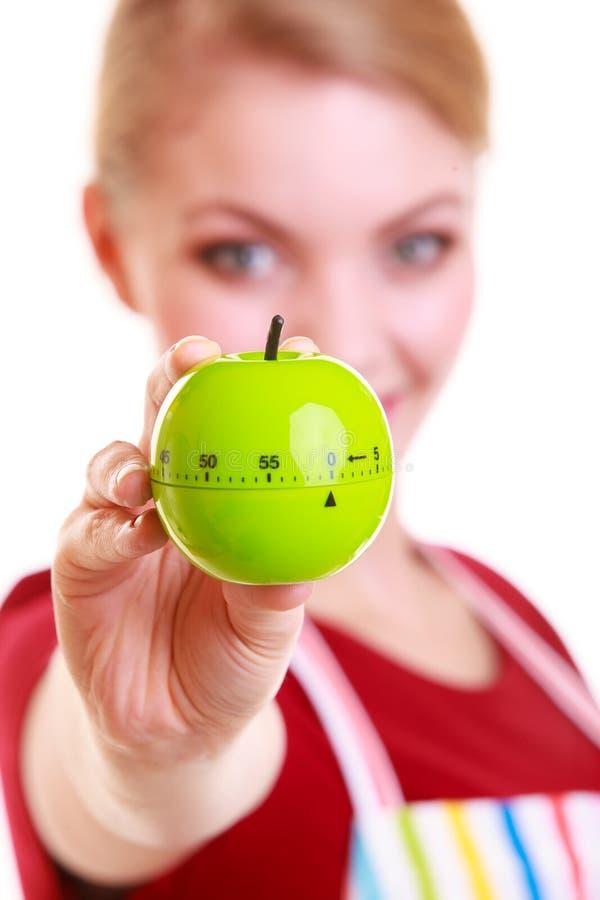 Femme au foyer ou chef heureuse dans le tablier de cuisine montrant la minuterie de pomme photo stock