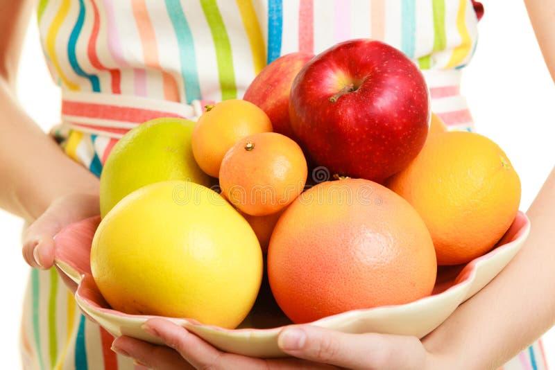 Femme au foyer ou vendeur offrant les fruits sains d'isolement photographie stock