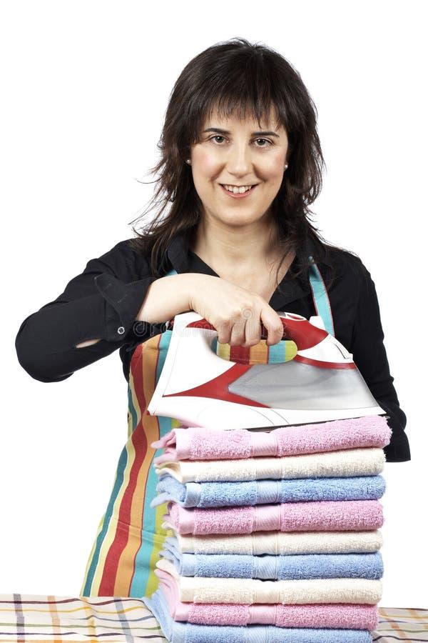 Femme au foyer près des essuie-main empilés photo stock
