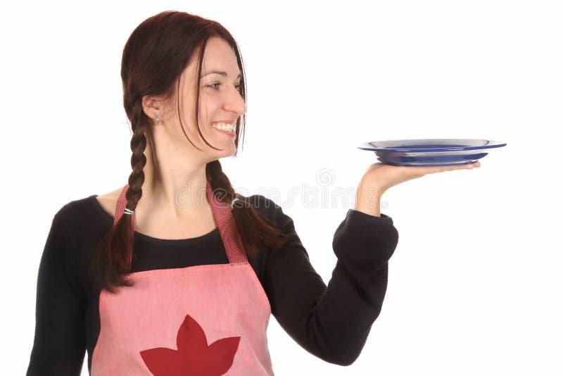 Femme au foyer retenant la plaque vide images stock