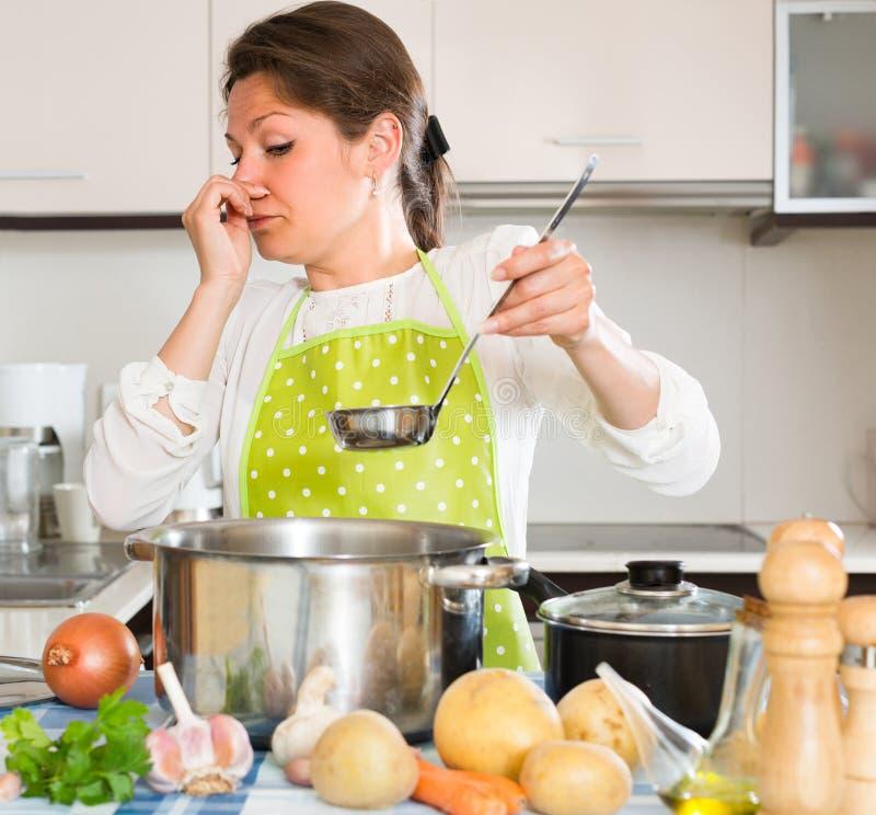 Femme au foyer sentant la mauvaise odeur de la casserole image libre de droits