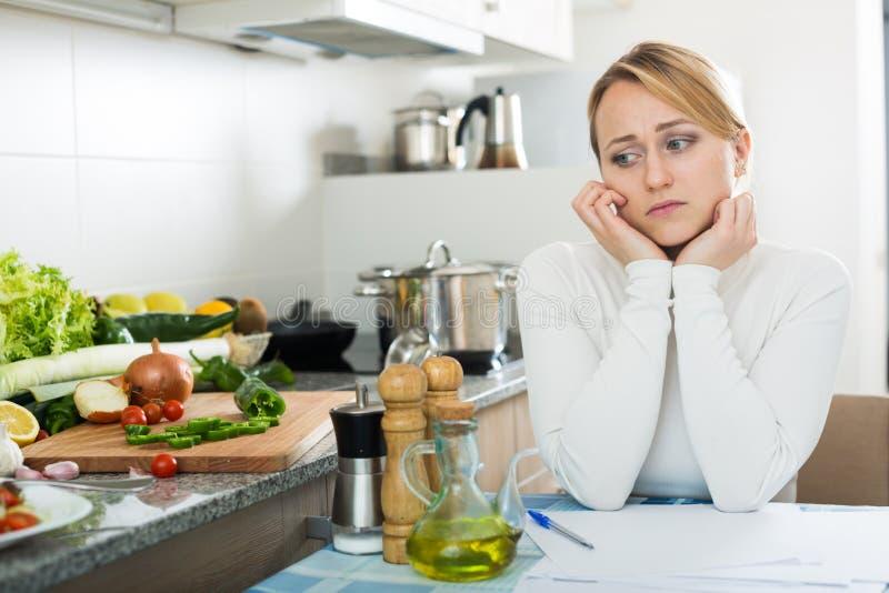 Femme au foyer triste avec des documents dans la cuisine images stock