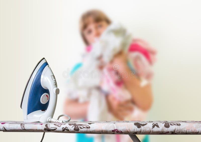 Femme au foyer Unfocused avec une pile de blanchisserie photos stock