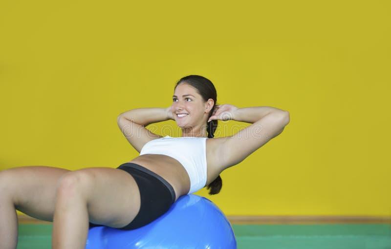 Femme au gymnase avec une boule de pilates photos stock