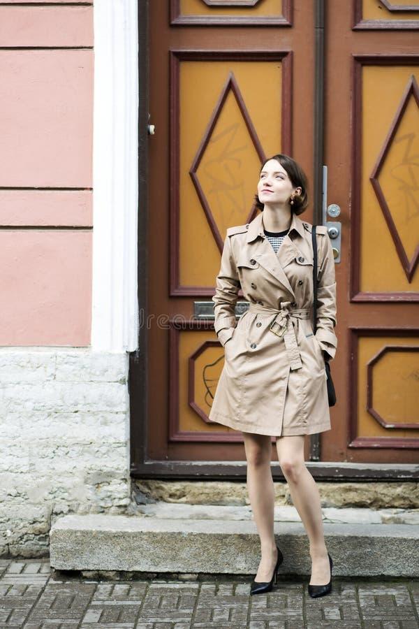 Femme au manteau avec le sac à main et les vieilles portes images libres de droits