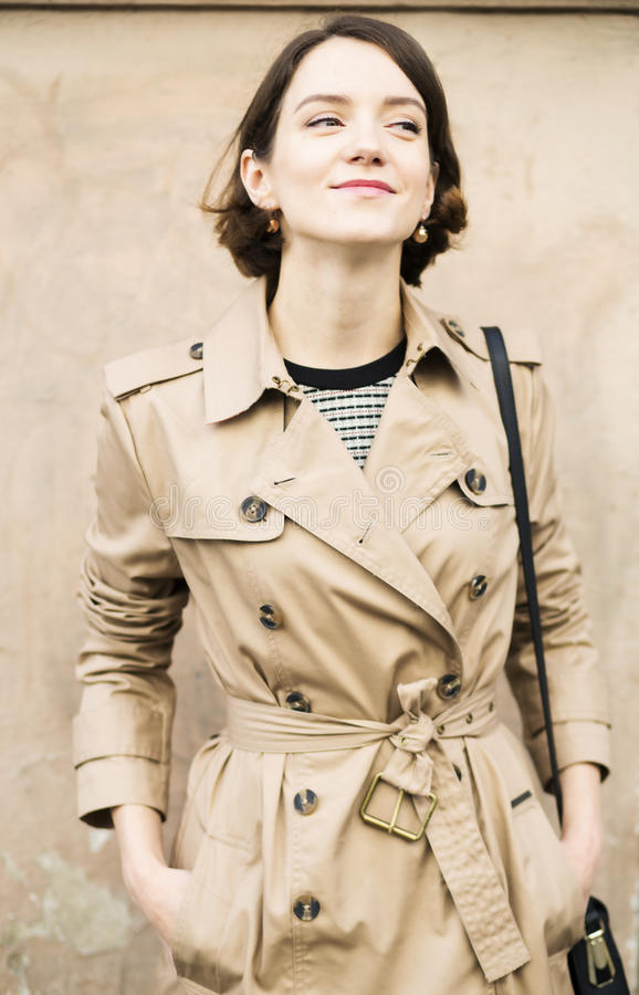 Femme au manteau beige avec le mouchard de sourire de sac à main images libres de droits