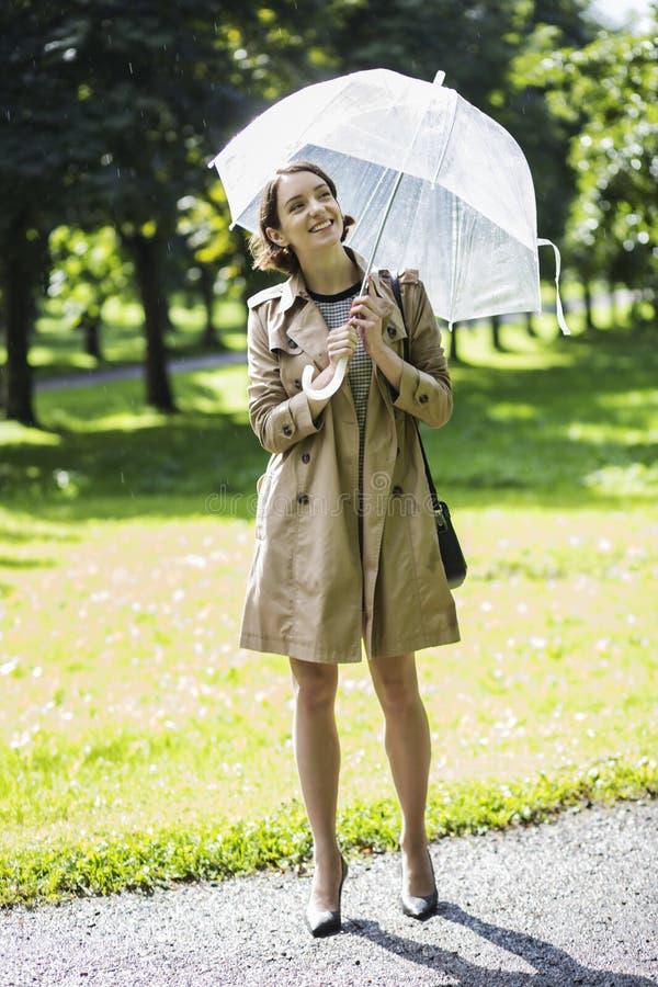 Femme au manteau beige avec le parapluie sous la lumière du soleil images libres de droits