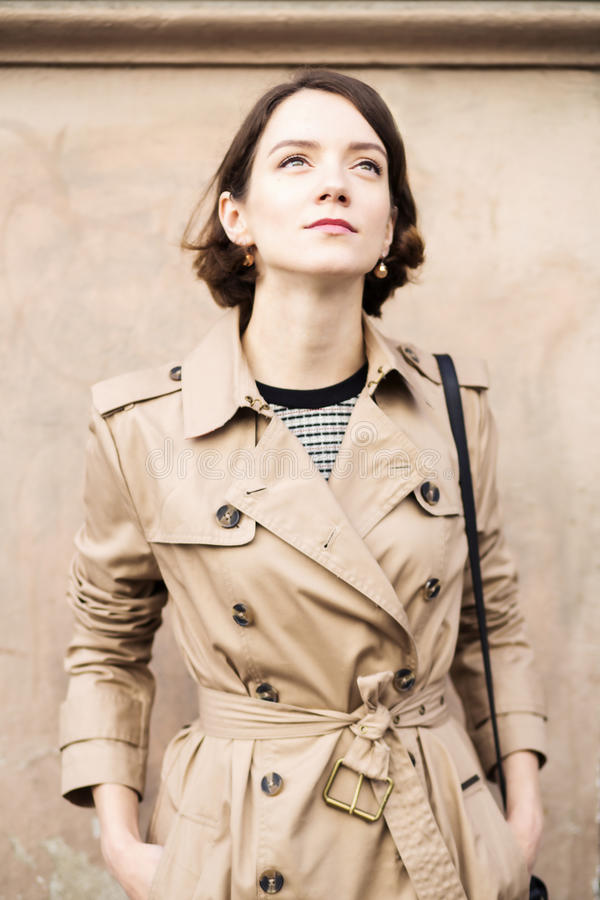 Femme au manteau beige avec le sac à main recherchant photos stock