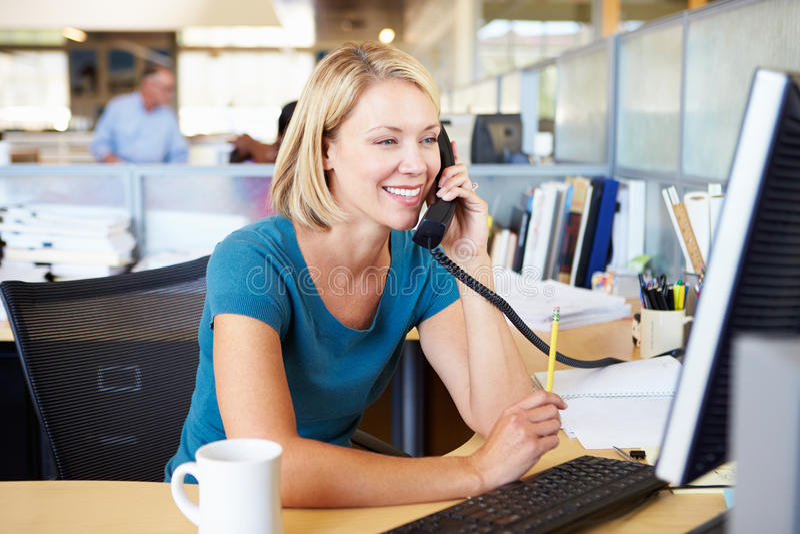 Femme au téléphone dans le bureau moderne occupé photos stock