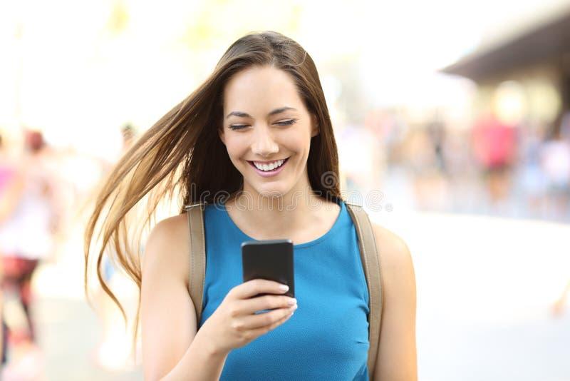 Femme au téléphone marchant sur la rue photo libre de droits