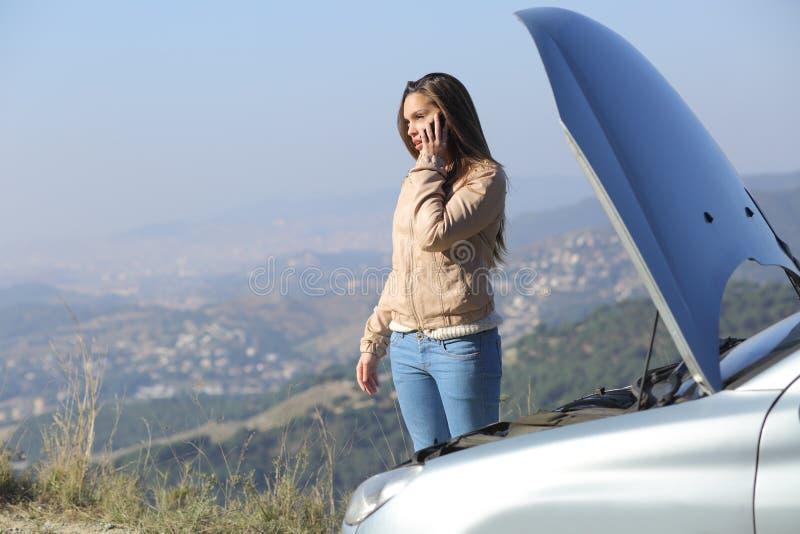 Femme au téléphone près d'une voiture de panne image stock