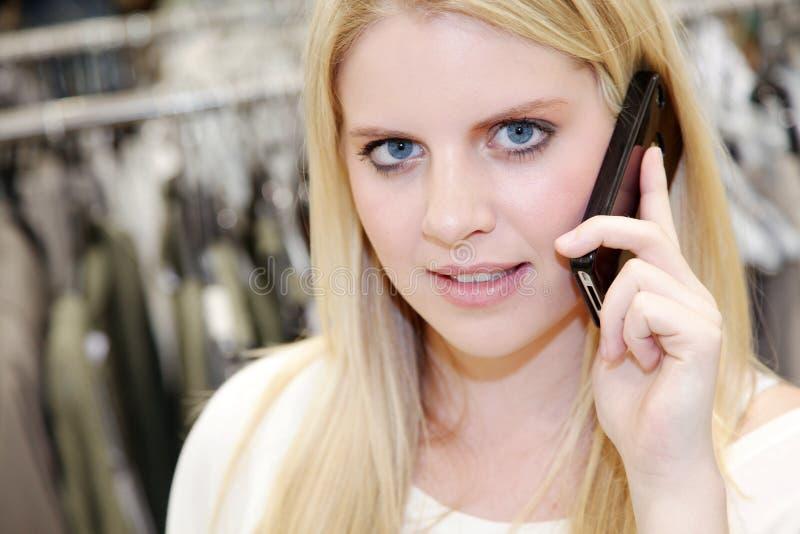 Femme au téléphone tout en faisant des emplettes photo libre de droits