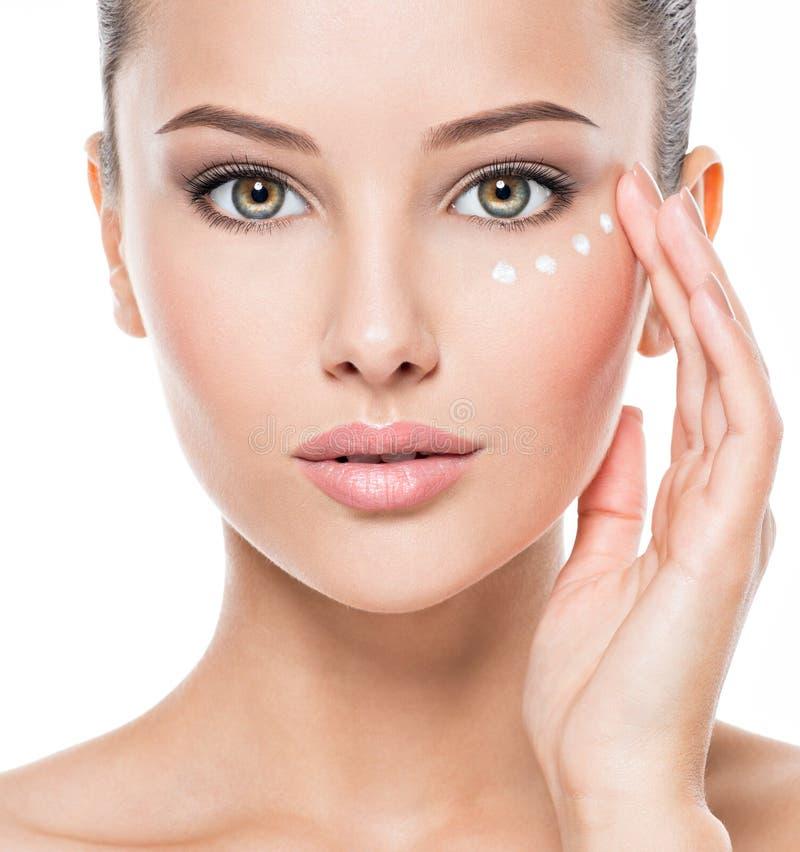 Femme au visage sain qui applique de la crème cosmétique sous les yeux photo libre de droits