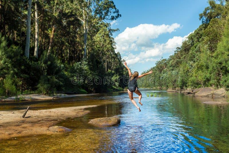 Femme australienne active sautant dans le bushland ? distance de rivi?re images libres de droits