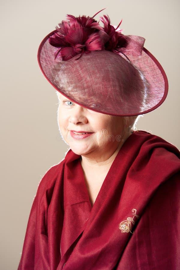 Femme aux cheveux blancs dans le chapeau et l'écharpe rouges photographie stock