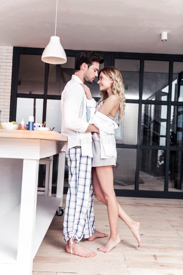 Femme aux cheveux longs blonde stupéfiante dans des vêtements à la maison intéressants étreignant son mari photos stock
