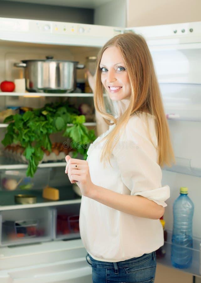 Femme aux cheveux longs recherchant quelque chose dans le réfrigérateur photo stock