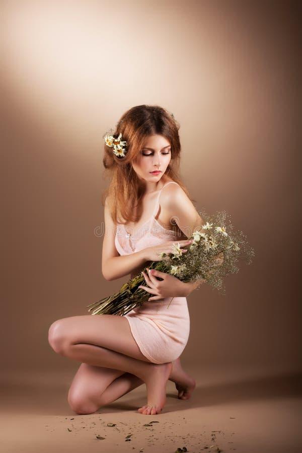 Femme aux pieds nus auburn sentimentale détendant avec des Wildflowers photo libre de droits