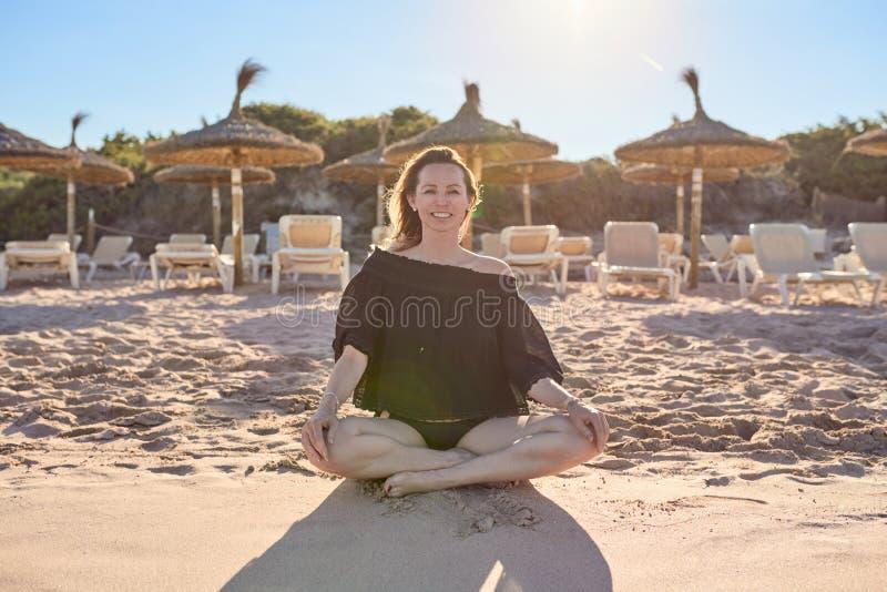 Femme aux pieds nus en bonne santé de sourire s'asseyant en tailleur sur la plage images libres de droits