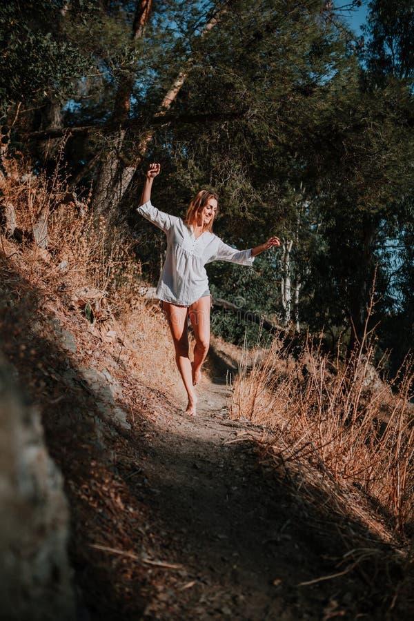 Femme aux pieds nus marchant et dansant le long du chemin étroit en nature photo stock