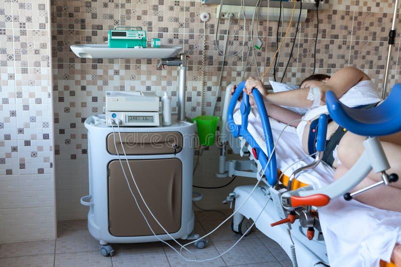 Femme avec accouchement difficile allongée sur un fauteuil de naissance avec une forte douleur abdominale, maternité clinique images libres de droits