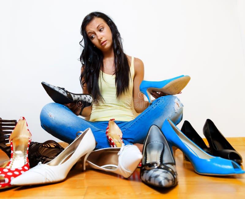 Femme avec beaucoup de chaussures à choisir de image stock