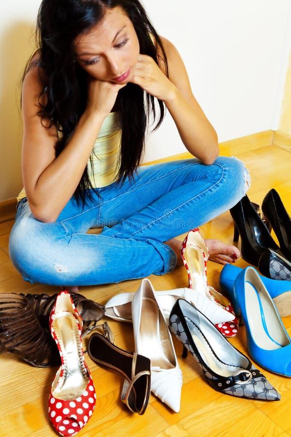 Femme avec beaucoup de chaussures à choisir de photographie stock