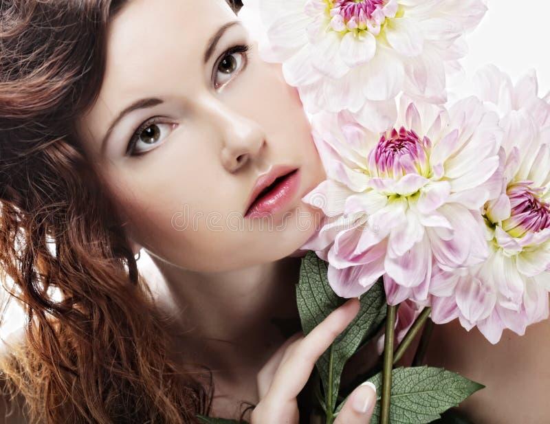 Femme avec de grandes fleurs roses photographie stock libre de droits