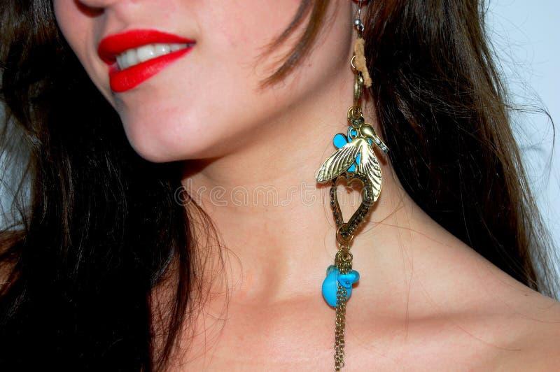 Femme avec de l'or et le bleu de boucle d'oreille image stock