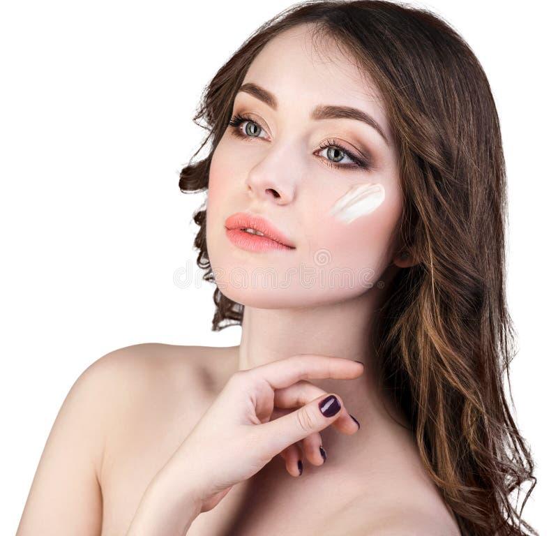 Femme avec de la crème cosmétique sur le visage photographie stock libre de droits