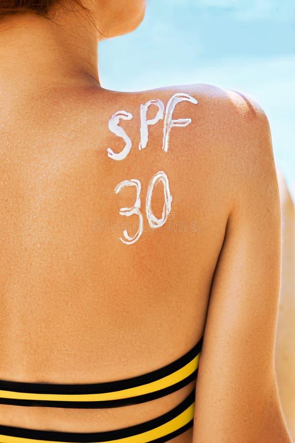 Femme avec de la cr?me de bronzage sous la forme de mot de la SPF 30 sur elle de retour au-dessus du fond de mer image stock